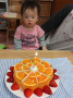 大きなケーキを前に、じーっとロウソクを見つめるにこちゃん。おめでとう!